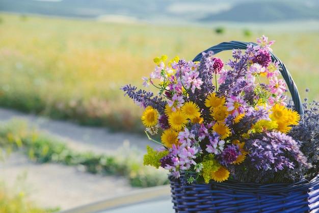 Polne kwiaty w koszyku. bukiet różnych kwiatów w koszu na polnej drodze. stonowany.