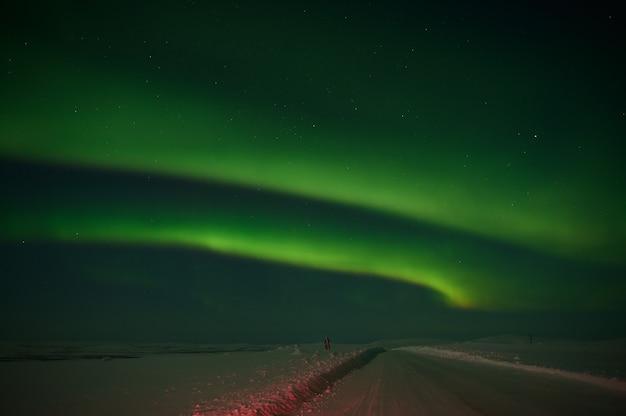 Północne światło na cichym polu przed wschodem słońca.