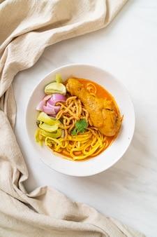 Północno-tajska zupa curry z makaronem z kurczakiem (kao soi kai) w stylu tajskim