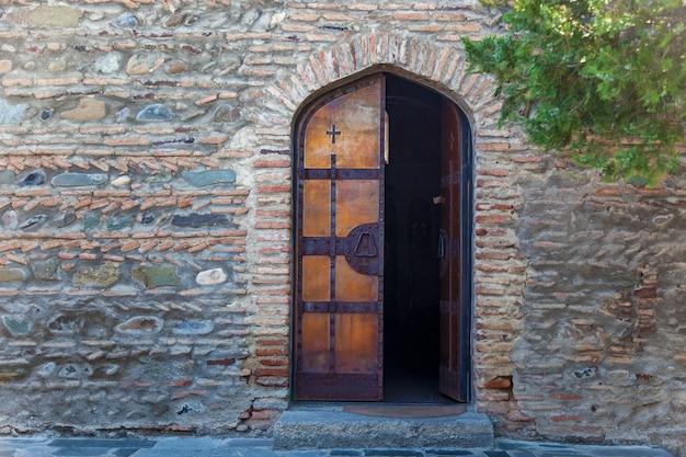 Półotwarte drewniane drzwi kościoła na tle kamiennego muru. drewniane drzwi kościoła.