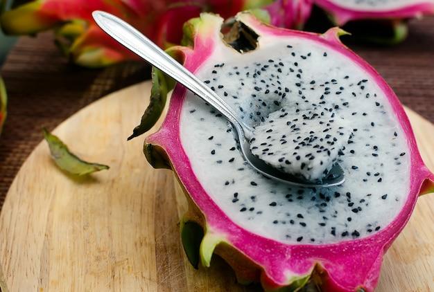 Połowa białego dragomfruit z łyżką na desce do krojenia