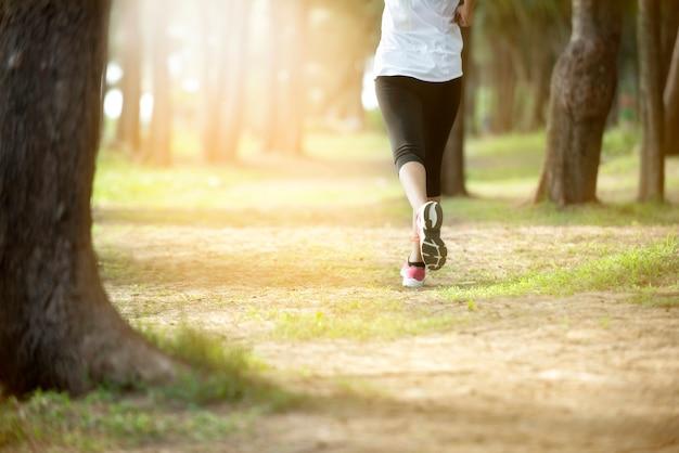 Połowa ciała runner nogi kobiety noszenie legging sport i sneaker kobiety biegnące w parku leśnym.