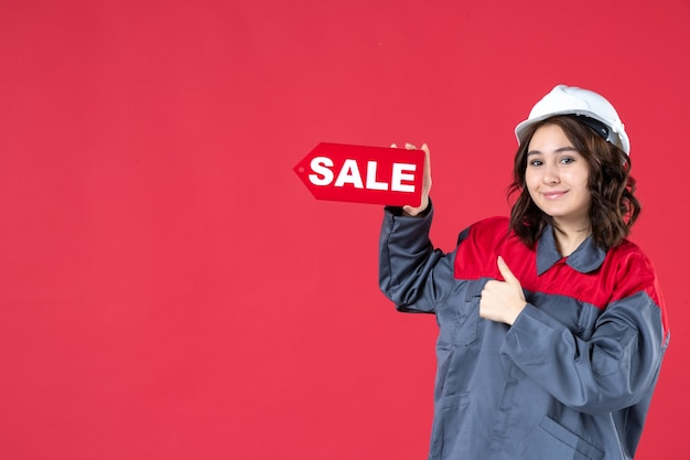 Połowa ciała strzał uśmiechnięta pracownica w mundurze nosząca twardy kapelusz i wskazująca ikonę sprzedaży, wykonując ok gest na na białym tle czerwonym tle
