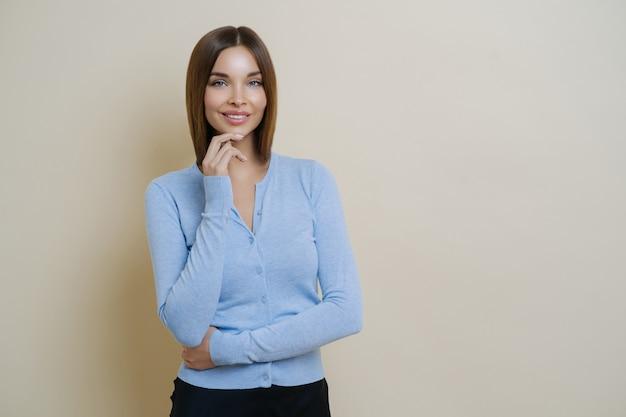Połowa długości piękna szczupła kobieta ubrana w swobodny niebieski sweter, trzyma rękę pod brodą
