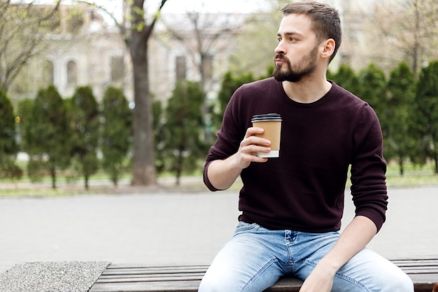 Połowa długości portret brodaty bloger w stylowych okularach przeciwsłonecznych, spacerując po ulicy z kawą na wynos i smartfonem w rękach. wesoły hipster facet ubrany w casual sprawdzanie powiadomienia na telefon