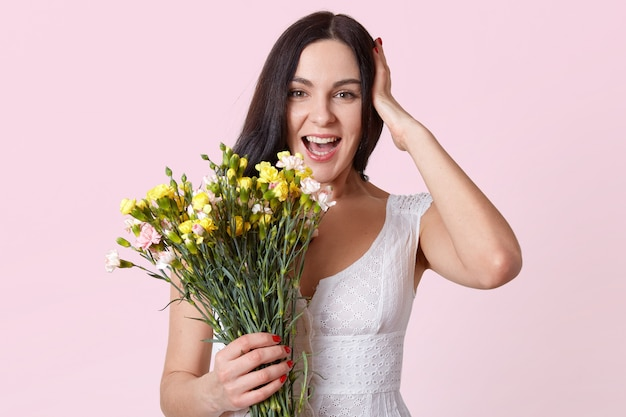 Połowa długości portret ładna brunetka kobieta trzyma bukiet kwiatów, śmiejąc się, patrząc bezpośrednio na kamerę, trzyma rękę na głowie