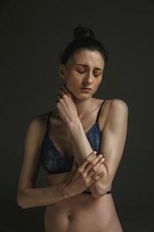 Połowa długości portret młodej kobiety smutne w bieliźnie na ciemnej ścianie. smutek, depresja i uzależnienie. pojęcie ludzkich emocji, feminizm, problemy i prawa kobiet, zdrowie psychiczne.