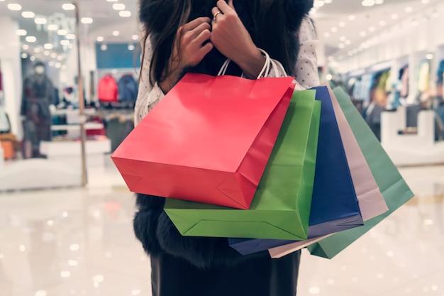 Połowa długości strzał dziewczyny trzymającej wiele papierowych toreb na zakupy w tle dzielnicy handlowej. młoda dziewczyna naciskając sterty worków do piersi w centrum handlowym. pani niosąca paczki z zakupami. kobieta dużo kupuje.