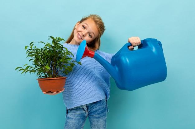 Połowa długości zdjęcia uczennicy z konewką do ogrodu i rośliny o niebieską ścianę