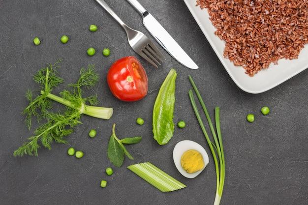 Połowa jaja pomidorowego i zioła na stole brązowy ryż w białym talerzu