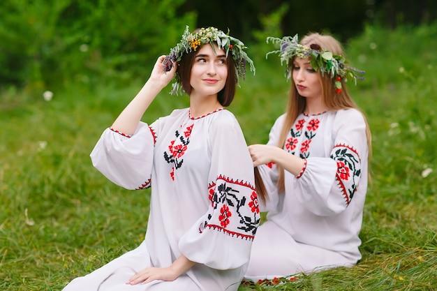 Połowa lata. dwie dziewczyny w słowiańskich ubraniach splatają warkocze we włosach przy ognisku.