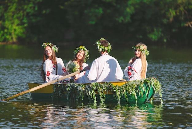 Połowa lata. grupa młodych ludzi w strojach ludowych pływa łodzią ozdobioną liśćmi i porostami. słowiańskie święto iwana kupały.