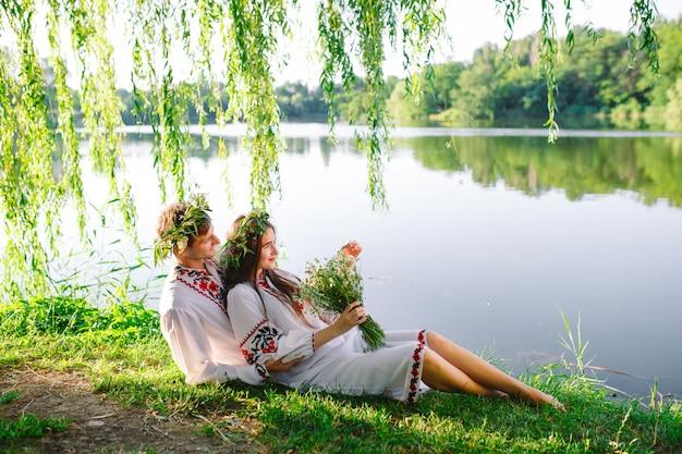 Połowa lata. młoda kochająca para w słowiańskich strojach na brzegu jeziora. słowiańskie święto iwana kupały.