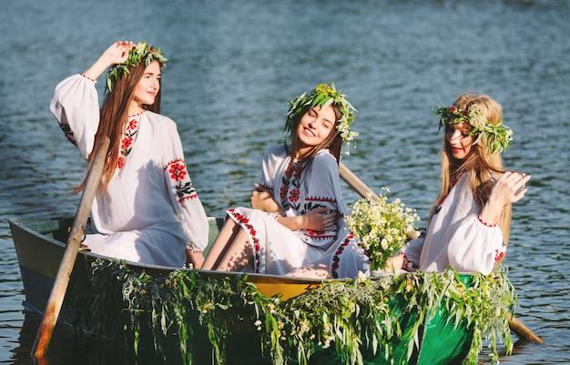Połowa lata. młode dziewczyny w strojach ludowych pływają łodzią ozdobioną liśćmi i porostami. słowiańskie święto iwana kupały.