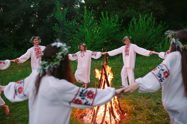Połowa lata. młodzi ludzie w kręgu strojów słowiańskich tańczą wokół ogniska w lesie.