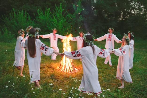 Połowa lata. młodzi ludzie w słowiańskich kręgach odzieżowych tańczą wokół ogniska w lesie.