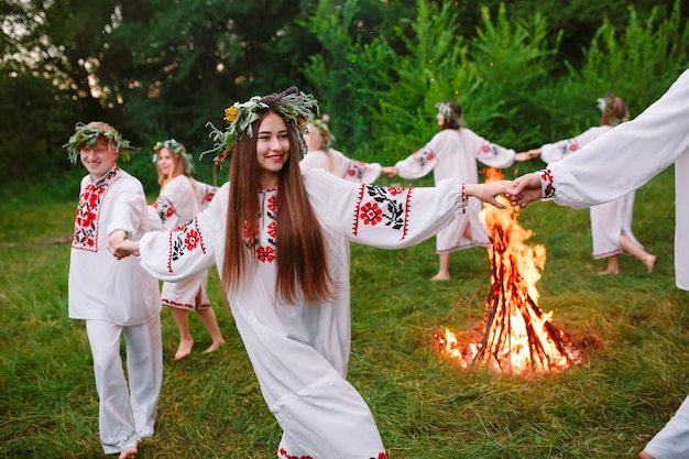Połowa lata. młodzi ludzie w słowiańskich ubraniach krążą wokół ogniska w środku lata. .