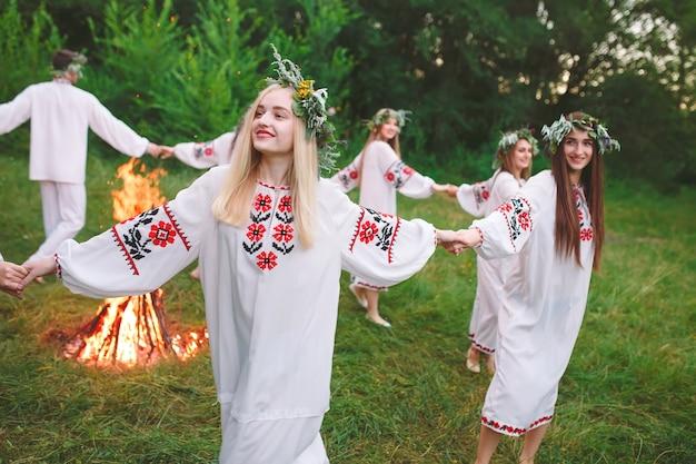 Połowa lata. młodzi ludzie w słowiańskich ubraniach obracają się wokół pożaru w środku lata. .