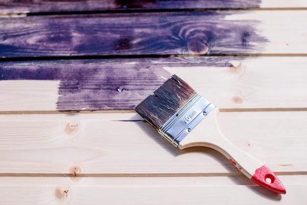 Połowa malowanej powierzchni drewnianej. głęboki czarny kolor.