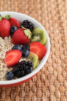 Połowa miski wypełniona owocami i płatkami zbożowymi
