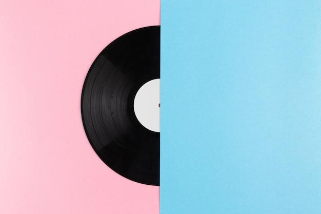 Połowa płyty winylowej na abstrakcyjnym kreatywnym pastelowym różu i niebieskim pastelowym tle