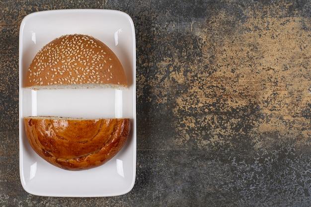 Połowa pokrojone świeże ciasto i drożdżówka na białym talerzu