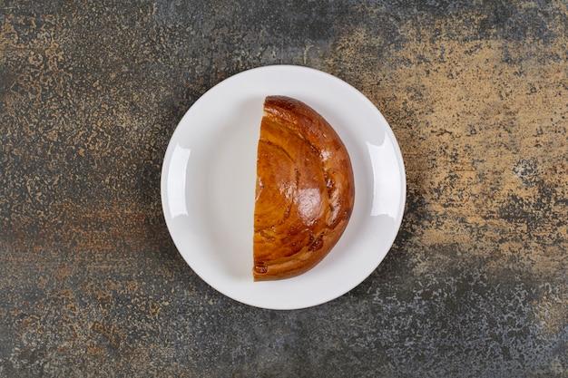 Połowa pokrojone świeże ciasto na białym talerzu