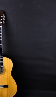 Połowa pomarańczowa gitara akustyczna na czarnym tle.