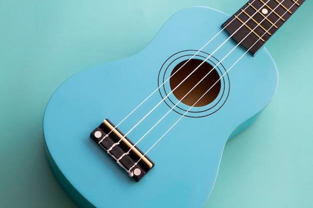 Połowa przednia strona niebieskiego ukulele z białymi strunami, na pastelowym tle, instrument akustyczny