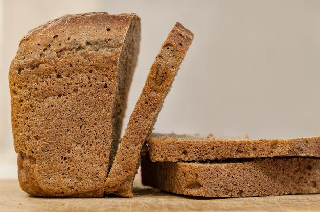 Połowa razowego chleba żytniego z kilkoma kromkami chleba na desce do krojenia.