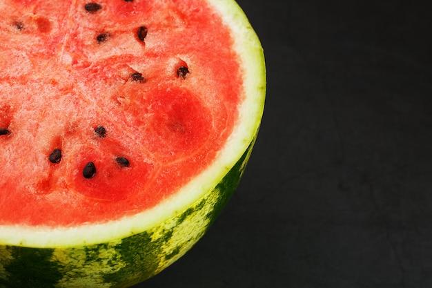 Połowa smacznego i dojrzałego czerwonego arbuza na czarnej, soczystej miąższu dojrzałego czerwonego arbuza z nasionami