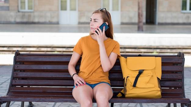 Połowa strzał kobieta na ławce rozmawia przez telefon na stacji kolejowej