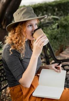 Połowa strzał kobiety na ławce picia kawy