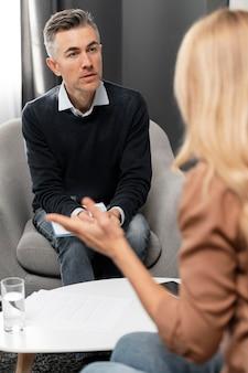 Połowa strzał terapeuty z schowka patrząc na kobietę