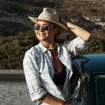 Połowa strzału blondynka kobieta stojąca przez okno samochodu