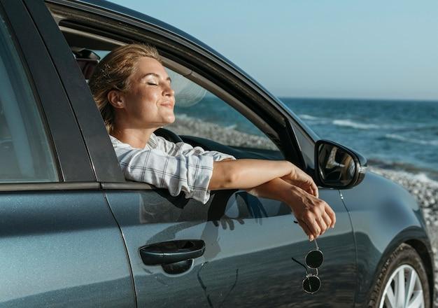 Połowa strzału blondynka w samochodzie patrząc na morze
