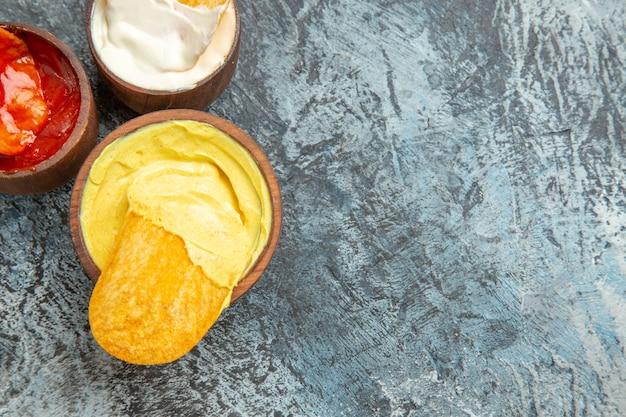 Połowa strzału domowej roboty chrupiące chipsy ziemniaczane keczup sos majonezowy na szarym stole