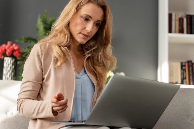 Połowa strzału doradca kobieta patrząc na laptopa