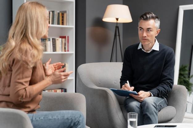 Połowa strzału kobieta rozmawia z terapeutą mężczyzna
