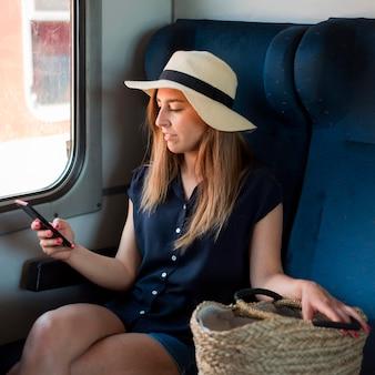 Połowa strzału kobieta siedzi w pociągu przy użyciu telefonu