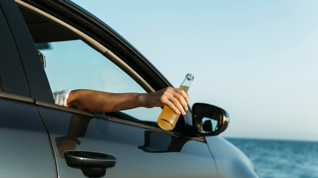 Połowa strzału kobieta trzyma butelkę soku poza oknem samochodu