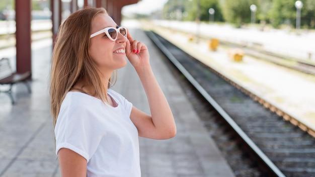 Połowa strzału kobieta uśmiecha się na stacji kolejowej