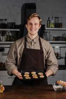 Połowa strzału kucharz trzyma tacę z ciasteczkami