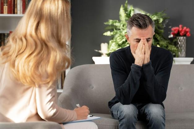 Połowa strzału mężczyzna siedzi na kanapie w gabinecie terapeutycznym w pobliżu terapeuty