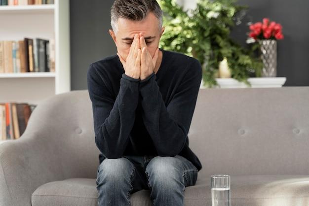 Połowa strzału mężczyzna siedzi na kanapie w gabinecie terapii