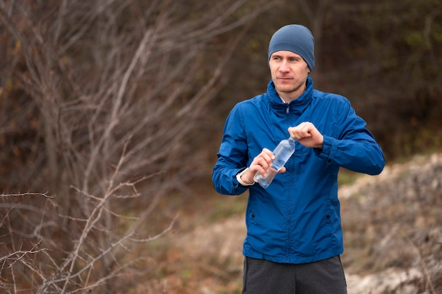 Połowa strzału mężczyzna trzyma butelkę wody w przyrodzie