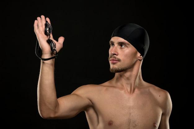 Połowa strzału pływaka trzymającego w ręku okulary