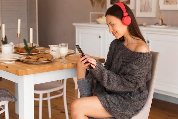 Połowa strzału przytulna kobieta siedzi na krześle i słucha muzyki