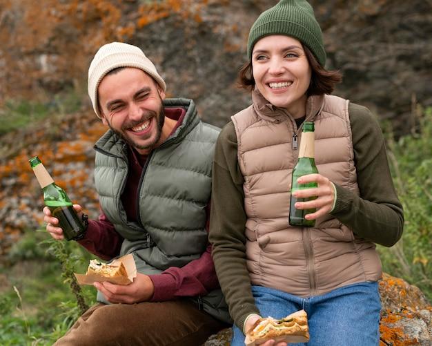 Połowa strzału szczęśliwa para siedzi na skale i popijając drinka
