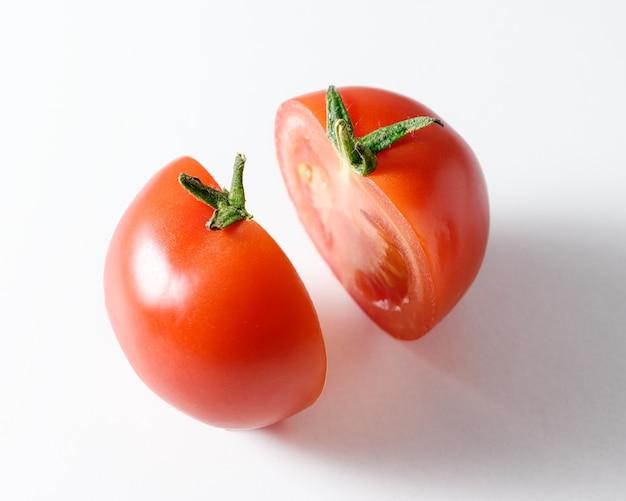 Połowa świeżych pomidorów na białej powierzchni.